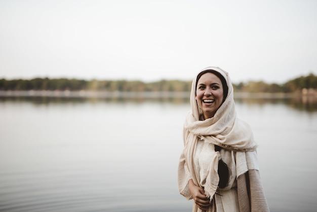 Ondiepe focus shot van een gelukkig wijfje dat een bijbelse jurk draagt en glimlacht