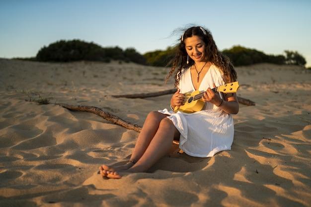 Ondiepe focus shot van een glimlachende vrouw in een witte jurk, zittend op een zanderige grond