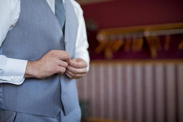 Ondiepe focus shot van een goed geklede man die zijn vest dichtknoopt