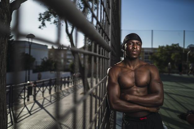 Ondiepe focus shot van een halfnaakte afro-amerikaanse man, leunend op het hek met gekruiste armen