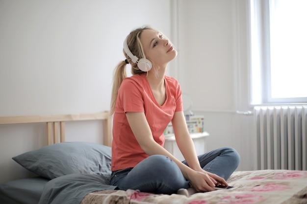 Ondiepe focus shot van een jonge vrouw, luisteren naar muziek in haar slaapkamer