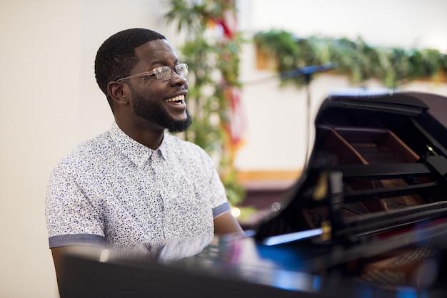 Ondiepe focus shot van een man die lacht tijdens het spelen van de piano