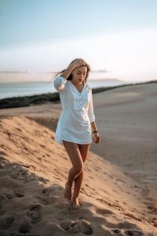 Ondiepe focus shot van een mooi meisje in het wit op de bea