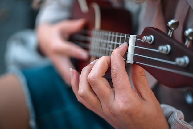 Ondiepe focus shot van een persoon die spijkerbroek draagt tijdens het afspelen van een liedje op de ukelele