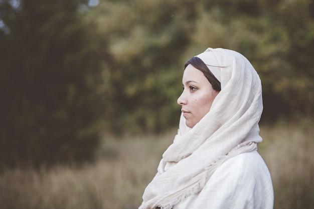 Ondiepe focus shot van een vrouw die een bijbelse mantel draagt en in de verte kijkt