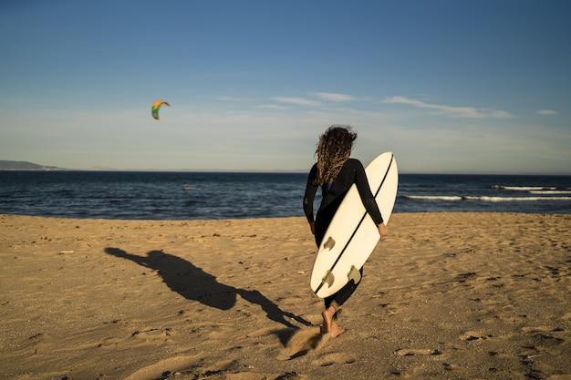 Ondiepe focus shot van een vrouw die een surfplank draagt tijdens het wandelen aan de kust in spanje