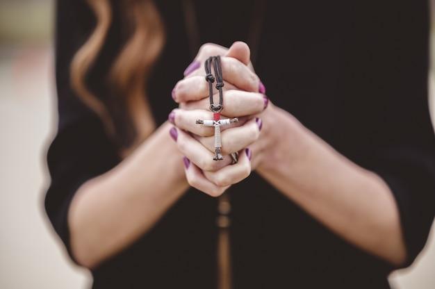 Ondiepe focus shot van een vrouw die een zwart shirt draagt terwijl ze een kruis in haar hand houdt