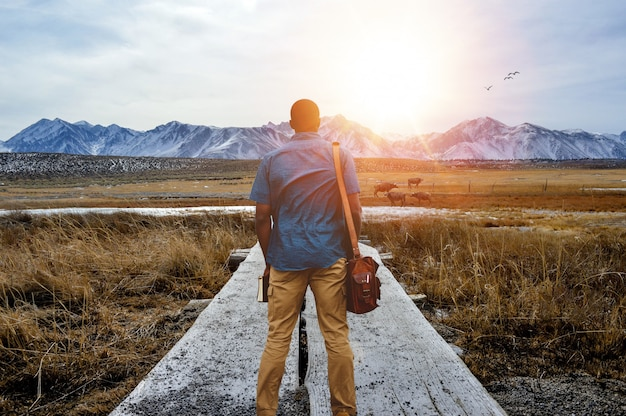 Ondiepe focus van achter van een man die op een pad in het midden van een grasveld