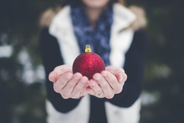 Ondiepe focus van de kerstbal van de persoon
