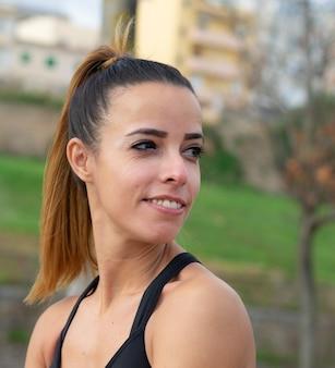 Ondiepe focus van een glimlachende vrouw die aan het trainen is in een park onder het zonlicht
