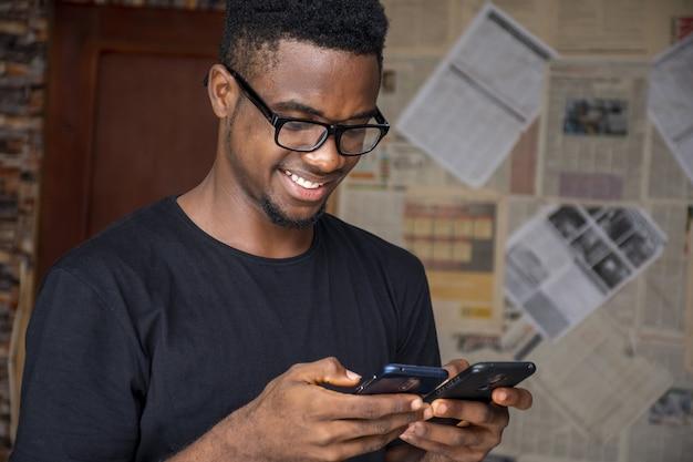 Ondiepe focus van een jonge afrikaanse man met een bril met twee telefoons in een kamer