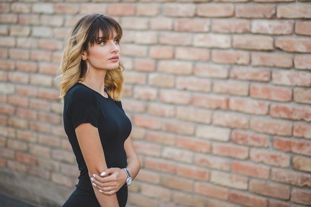 Ondiepe focus van een jonge bosnische vrouw met een bakstenen muurachtergrond