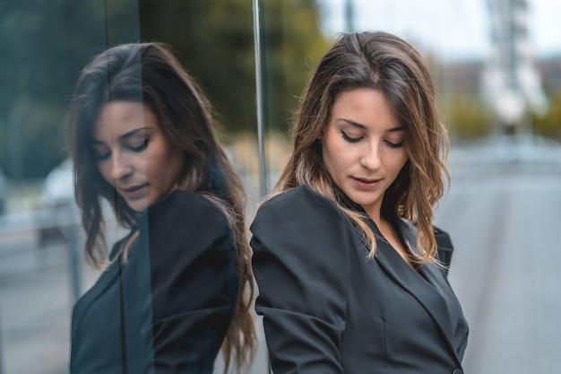 Ondiepe focus van een jonge vrouw in een zwarte jurk die poseert in de buurt van een modern gebouw met glazen wanden