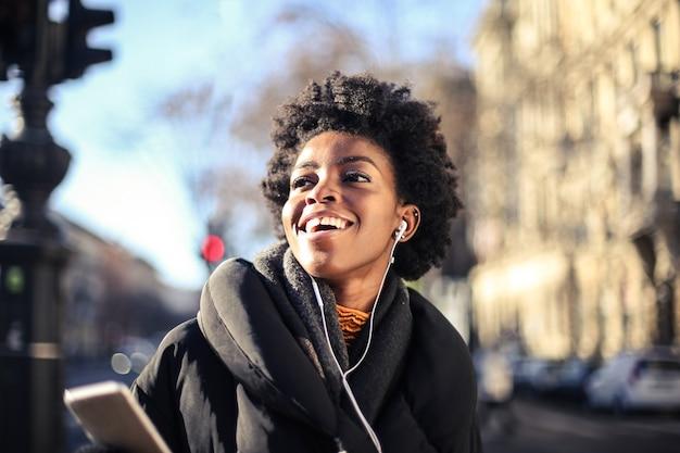 Ondiepe focus van een lachende afrikaanse vrouw met kort krullend haar die naar muziek luistert met een koptelefoon