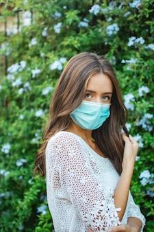 Ondiepe focus van een volwassen brunette vrouw die een kanten shirt met gezichtsmasker draagt en buitenshuis poseert
