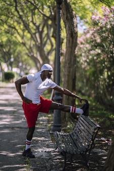 Ondiepe focus verticale shot van een afrikaans-amerikaanse man in een wit overhemd die zich uitstrekt op een bankje