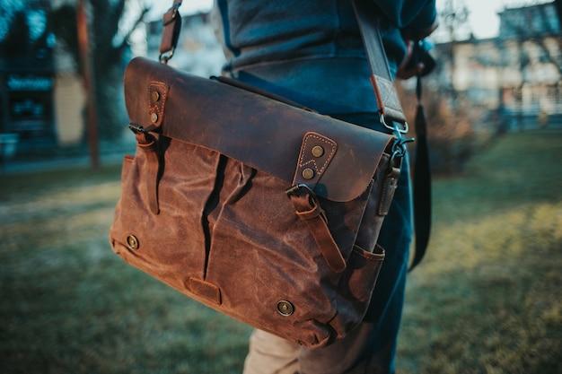 Ondiepe focus weergave van een man met een bruine lederen tas