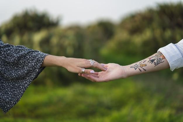 Ondiepe focusopname van de handen van twee mensen die naar elkaar reiken