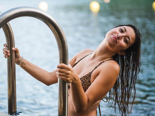 Ondiepe focusopname van een aantrekkelijke blanke vrouw die uit het zwembad stapt