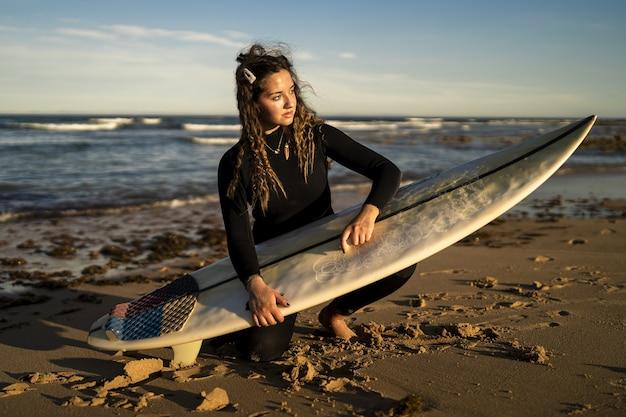 Ondiepe focusopname van een aantrekkelijke vrouw die haar surfplank in de was zet op het strand in spanje
