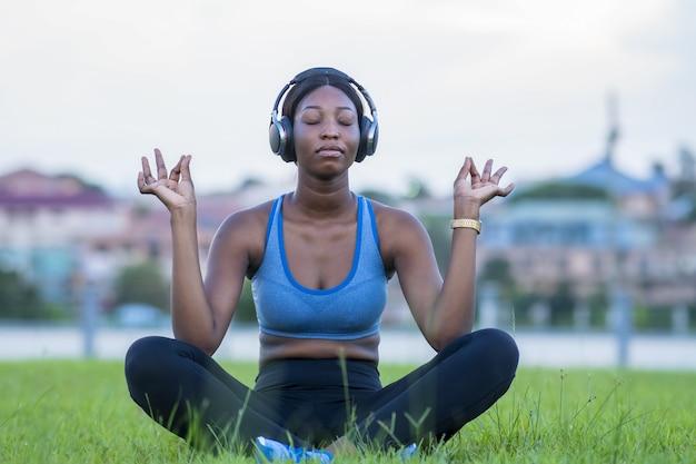 Ondiepe focusopname van een afrikaanse vrouw die mediteert terwijl ze op het gras in een park zit