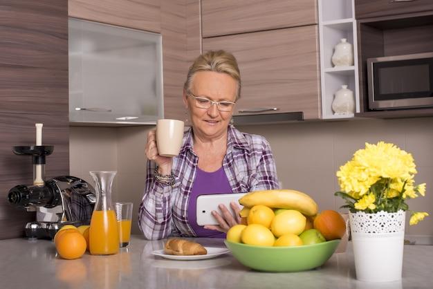 Ondiepe focusopname van een grootmoeder die naar de smartphone kijkt