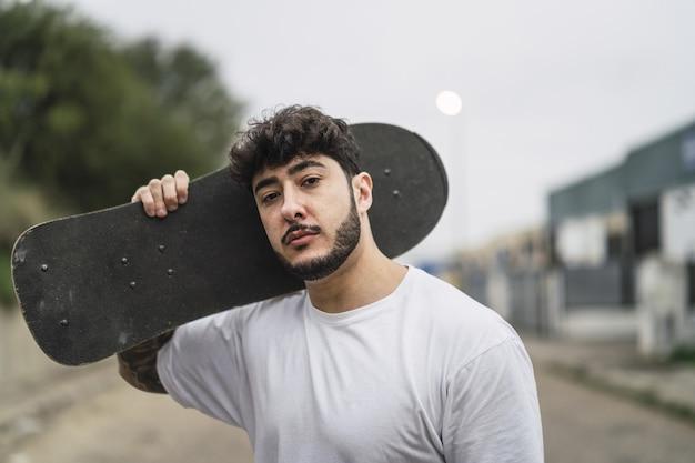 Ondiepe focusopname van een knappe europese skater die poseert met een skateboard in handen