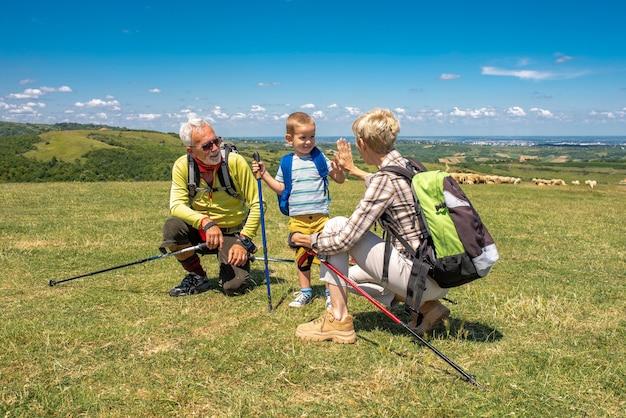 Ondiepe focusopname van een ouder echtpaar met hun kleinzoon in een groot veld