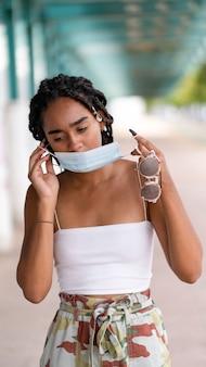 Ondiepe focusopname van een vrouw met dreadlocks en een masker dat voor de camera poseert