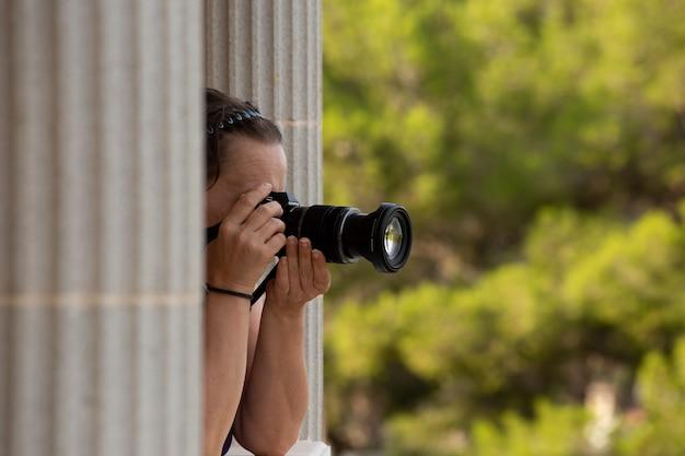 Ondiepe focusopname van een vrouwelijke fotograaf die foto's van de natuur maakt