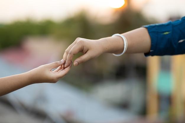 Ondiepe focusopname van twee handen die elkaar zachtjes aanraken