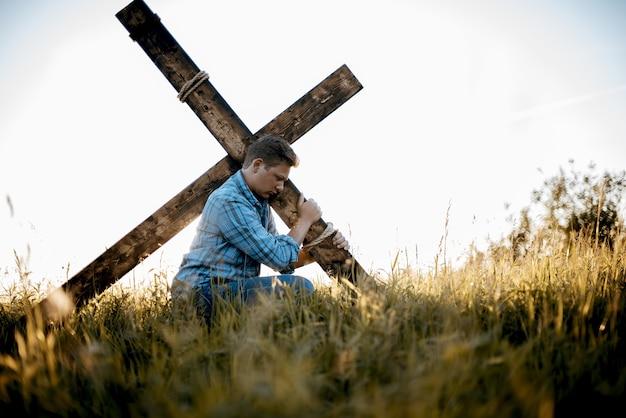 Ondiepe scherpstelling van een man die een handgemaakt kruis draagt