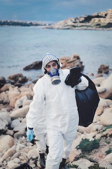 Ondiepe scherpstelling van een vrouw in speciaal uniform die het strand schoonmaakt