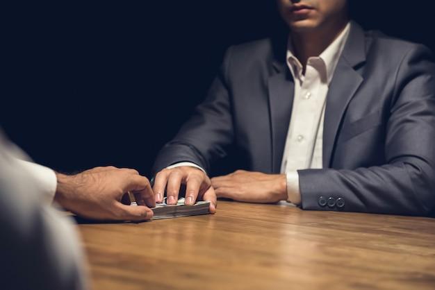 Oneerlijke zakenman die in het donker zijn partner in het donker geld geeft