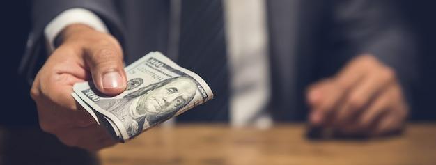 Oneerlijke zakenman die in het geheim geld in het donker weggeeft