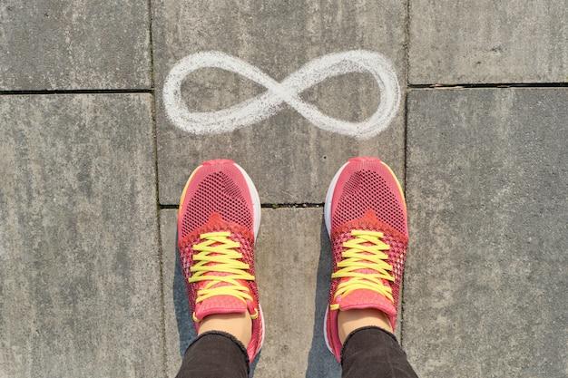 Oneindigheidsteken op grijze stoep met vrouwenbenen in tennisschoenen