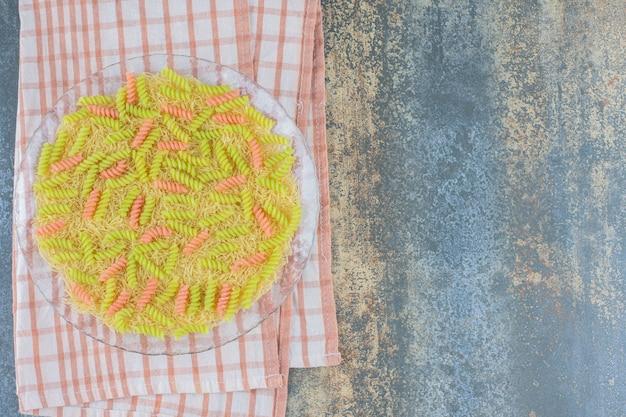 Ongebakken fusilli pasta in de glazen kom, op handdoek, op de marmeren achtergrond.