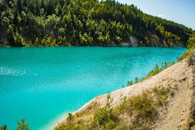 Ongebruikelijk meer met turkoois water in de krater. rotsachtige steenachtige kustkalksteengroeve in wit-rusland.
