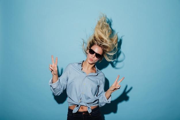 Ongebruikelijke blondevrouw in overhemd en zonnebril die vredesgebaren tonen