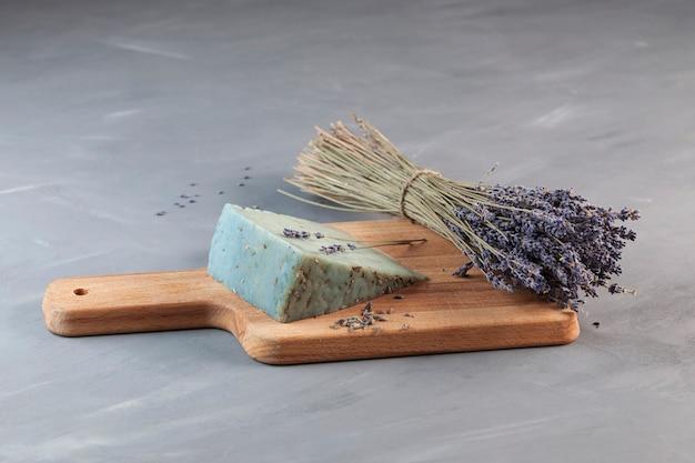 Ongebruikelijke schimmelkaas met lavendelsmaak op houten snijplank naast boeket van geurige lavendel.