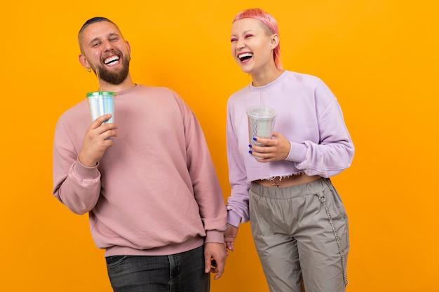 Ongebruikelijke vrouw met kort roze haar en tatoeage drinkt koffie en plezier met haar vriendje geïsoleerd op oranje