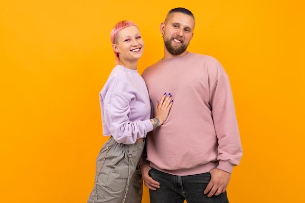 Ongebruikelijke vrouw met kort roze haar en tatoeage geniet van het leven met haar vriendje geïsoleerd op oranje