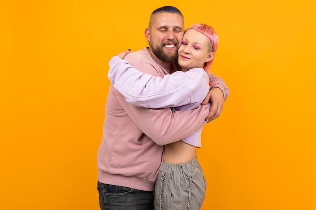 Ongebruikelijke vrouw met kort roze haar en tattoo knuffels met haar vriendje geïsoleerd op oranje