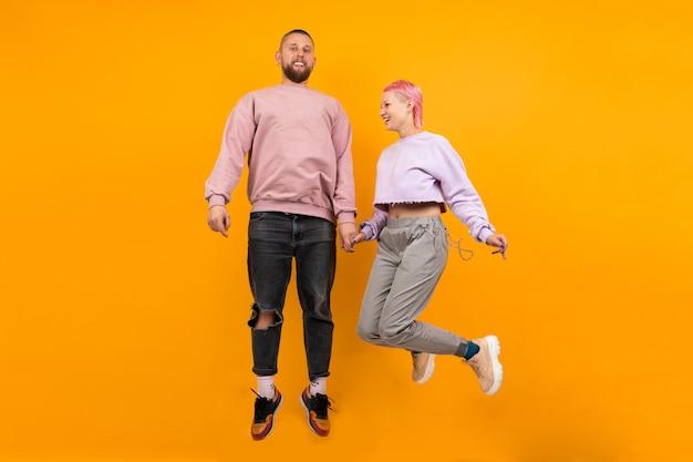 Ongebruikelijke vrouw met kort roze haar en tattoo springt met haar vriendje geïsoleerd op oranje.