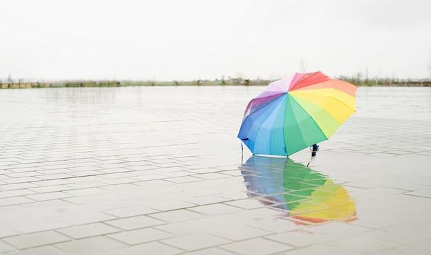 Ongebruikte kleurrijke paraplu die op grond ligt waarop wordt geregend. regenboogkleurige paraplu liggend in plassen op de natte straatgrond. ruimte kopiëren