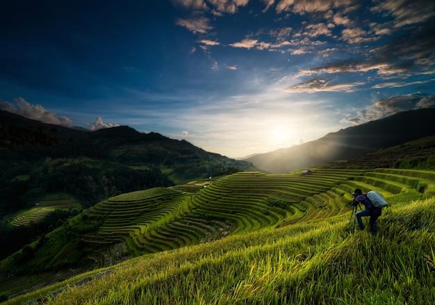 Ongedefinieerde fotograaf die een foto maakt over de rijstvelden op terrassen