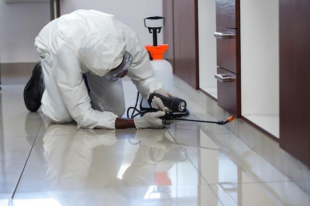 Ongediertebestrijdingsmens die pesticide onder het kabinet bespuiten