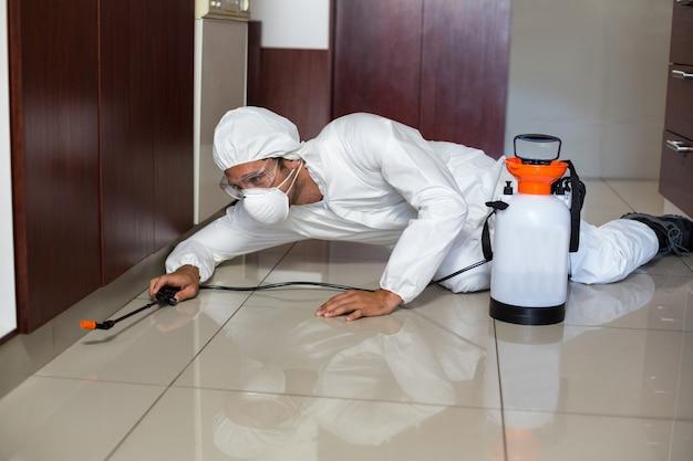 Ongediertewerker die spuitbus in keuken gebruiken