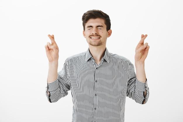 Ongeduldig bezorgd aantrekkelijke europese man met baard en snor, ogen sluiten en tanden op elkaar klemmen terwijl hij de vingers kruist en hoopt of doet wensen om een droom waar te maken