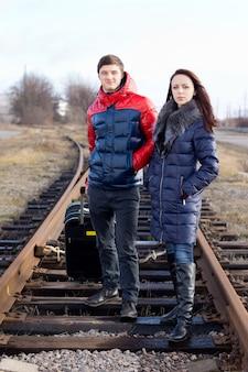 Ongeduldig jong stel wacht op de treinrails met hun ingepakte tas op de trein om aan hun jaarlijkse vakantie te beginnen